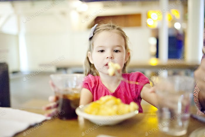 little girl eating mac and cheese in a restaurant