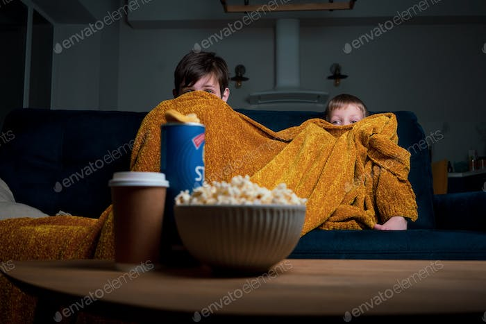 Horror movie night. Two boys watching movie with popcorn and potato chips