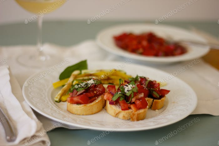 Bruschetta and wine on table with white placemats