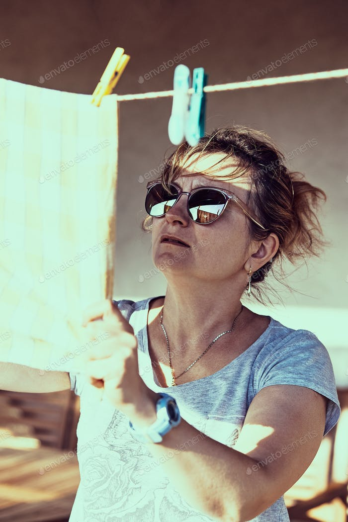 Mujer adulta que cuelga un paño blanqueado en el tendedero. Gente real, situaciones reales y auténticas