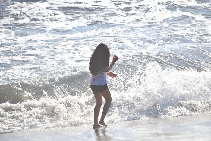 Girl playing with waves and bracing for the big splash