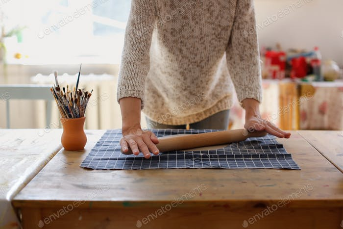 rolling clay with a rolling pin on the fabric on the table