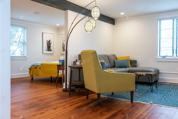 Open Concept Studio Layout - pops of yellow and turquoise and real wooden floors and white walls
