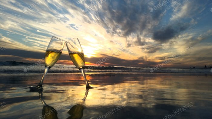 Two goblets wine toasting in the sea.