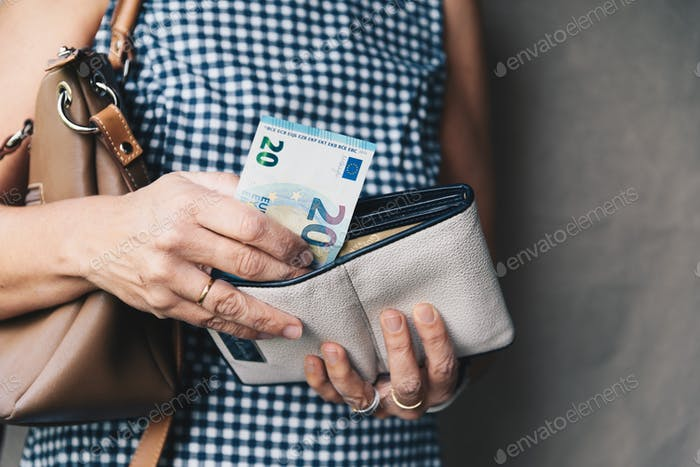 Closeup photo of stylish woman taking money out the wallet