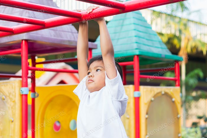 Kid exercise for health and sport. Happy Asian child boy play and hanging from bar at the playgroud