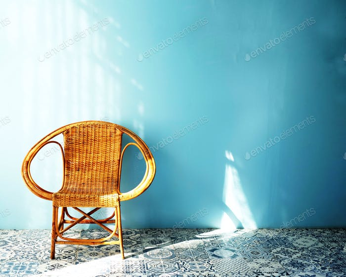 A small rattan chair on the floor with blue background