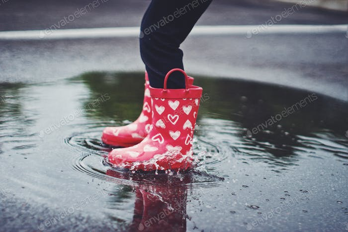 child in rain boots hopping in a puddle.