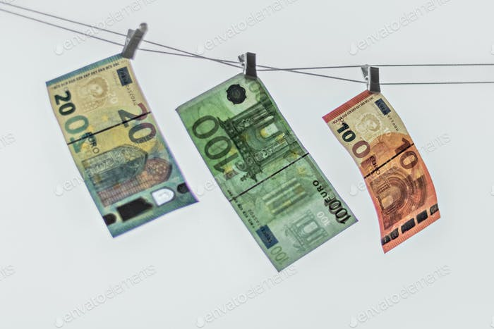 Euro banknotes hang on a clothesline on a white background. Euro money with clothespins on a rope.