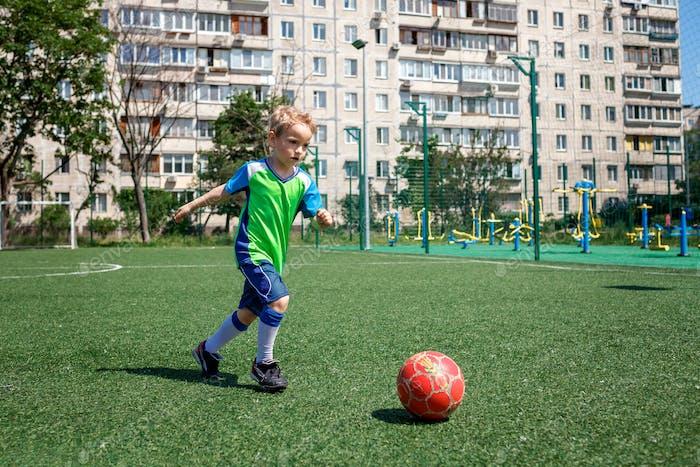 Niño en forma azul y verde jugando al fútbol en campo abierto en el patio, un joven futbolista