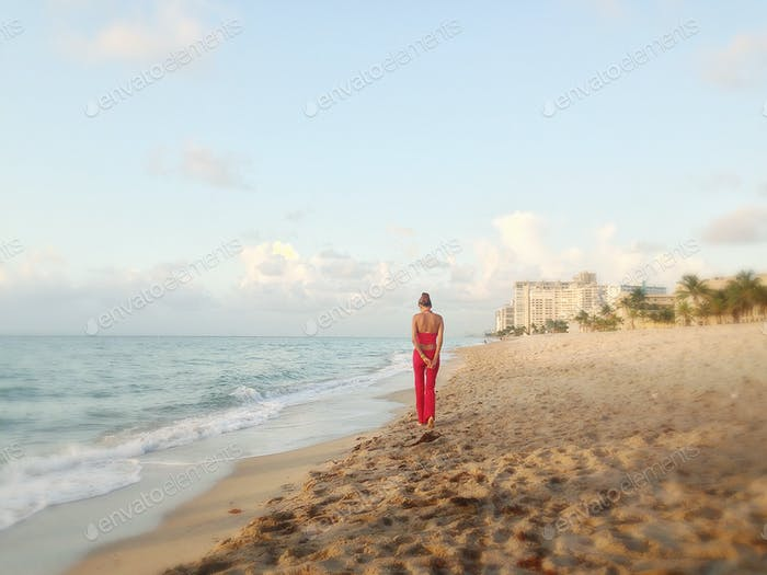 Lady in red walking along the shoreline