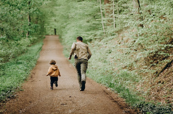 Father and son run through the forest