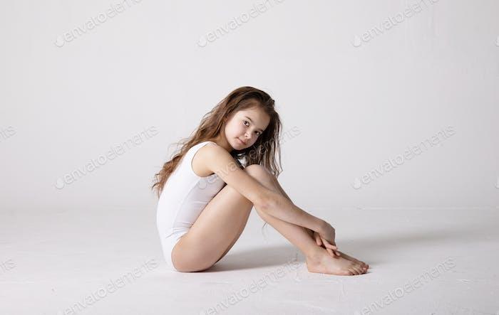 preteen girl gymnast trains on white background in white leotard. children's professional sports.