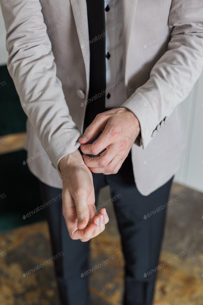 Groom fixing his sleeves. Velvet jacket.