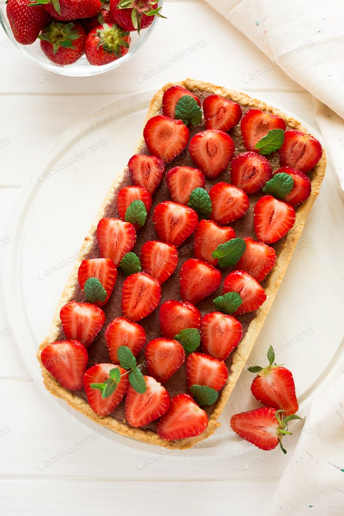 Homemade tart with strawberries and strawberry curd decorated mint leaves on white wooden background