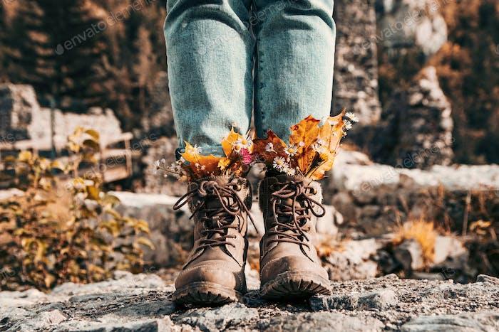 Вид спереди сапоги с осенними листьями и цветами, заправленными.