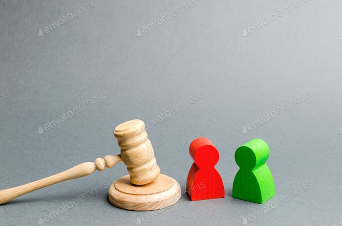 Wooden figures of people standing near the judge's gavel