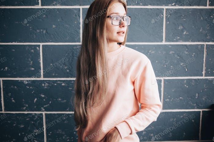 Mädchen mit rosafarbenem Sweatshirt und Brille auf minimalem Hintergrund