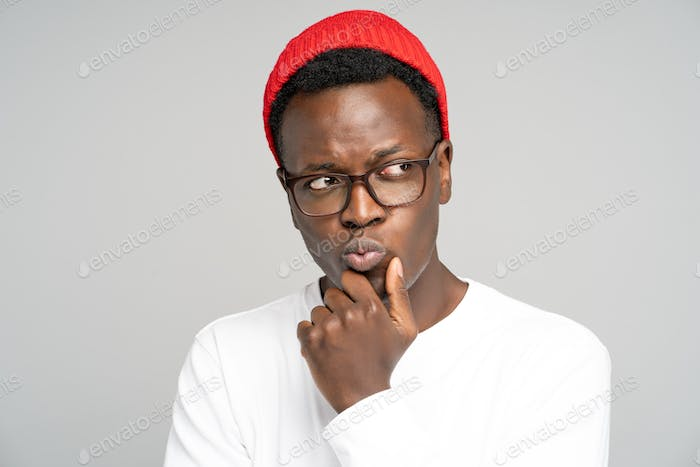 Unsure doubtful Black man in red hat wear glasses holds chin, looking right doubtfully