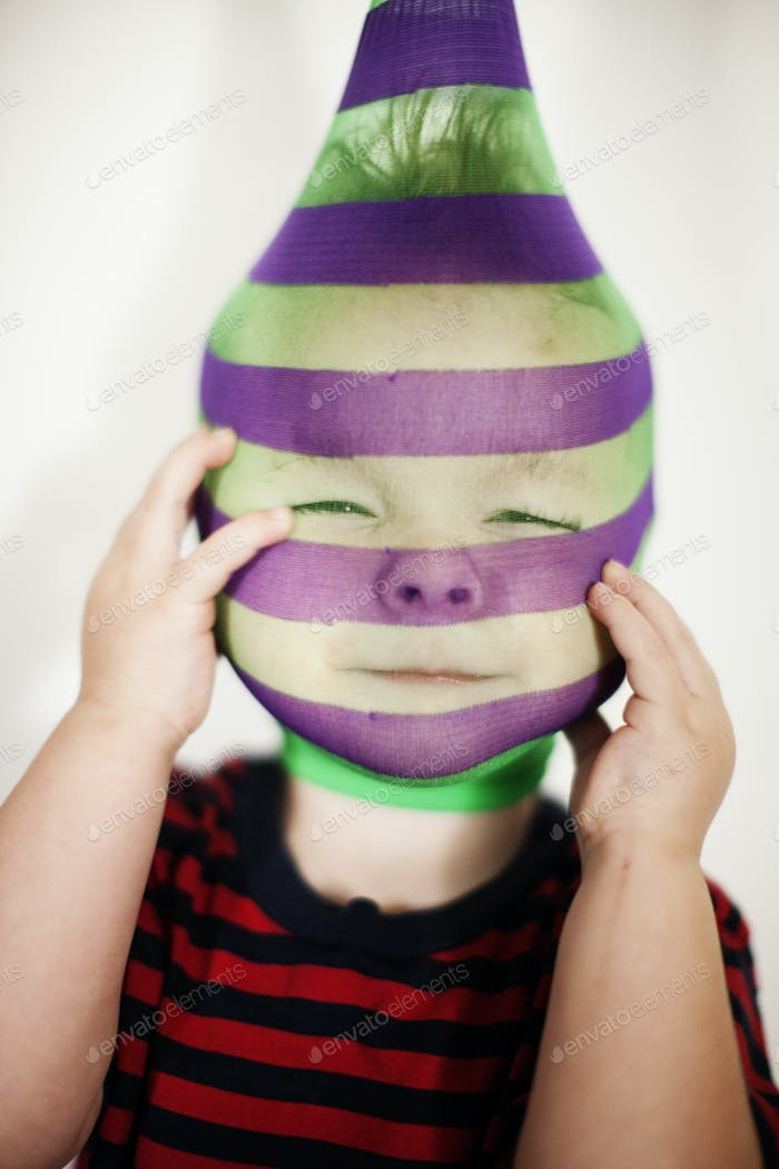 toddler wearing a stripped stocking on his head and looking like a bizarre bank robber.