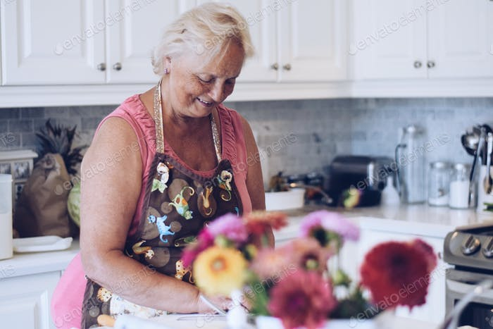 A happy woman is smiling while baking in a bright white modern kitchen. Seniors lifestyle