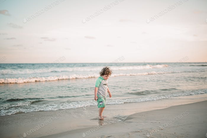 Boy playing in sand on beach