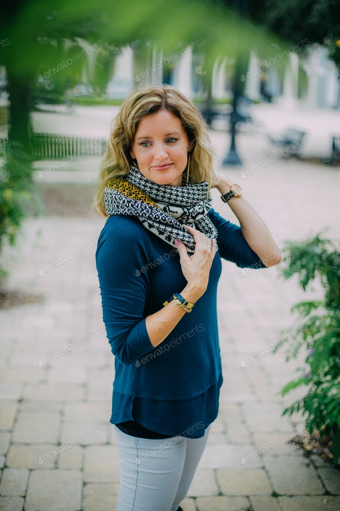 Lifestyle portrait of a stylish woman in her 40s wearing a scarf.