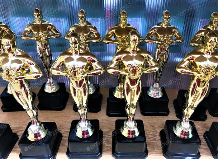 Many souvenir fake statuettes of the Oscar cinematic prize in the store on the shelf