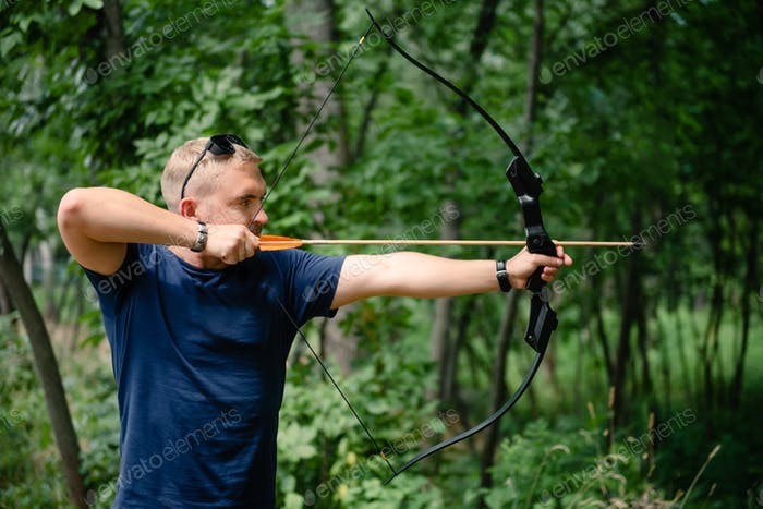 Archer man training with the bow in the forest