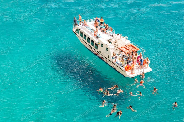 Summer Cruise Boat And Tourists Swimming In The Sea