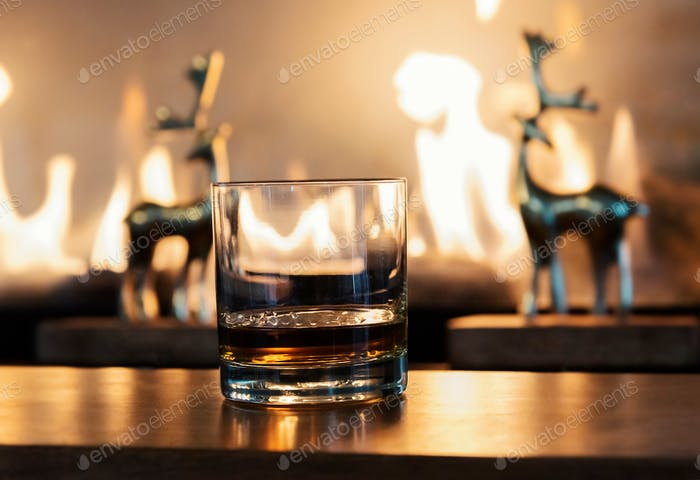 Whiskey neat by the fireplace with stag deer sculptures