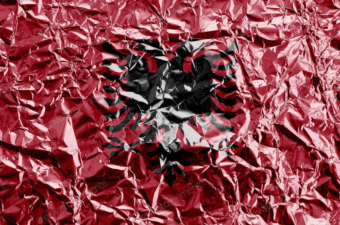 Albania flag depicted in paint colors on shiny crumpled aluminium foil close up