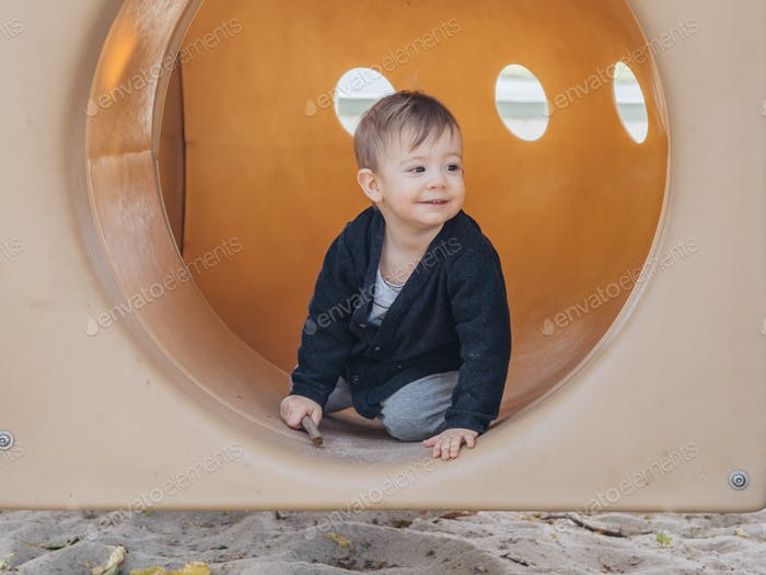 A young toddler at the playground of the park