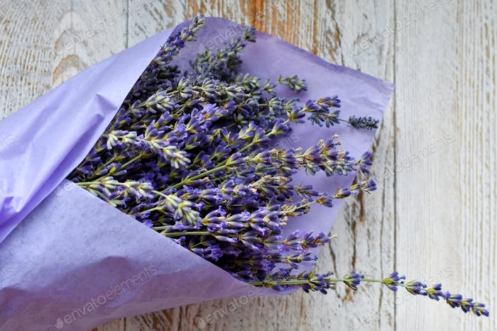Lavender bouquet wrapped in purple tissue paper on white distressed wooden plank table
