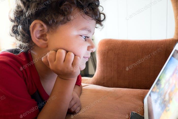 Vierjähriger Junge, der eine Show auf einem Tablet beobachtet