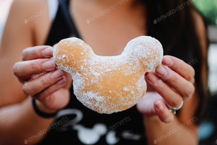 A freshly fried beignet covered in powdered sugar ready to be eaten for dessert at an amusement park