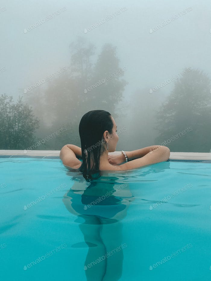 A beautiful woman in an outside swimming pool