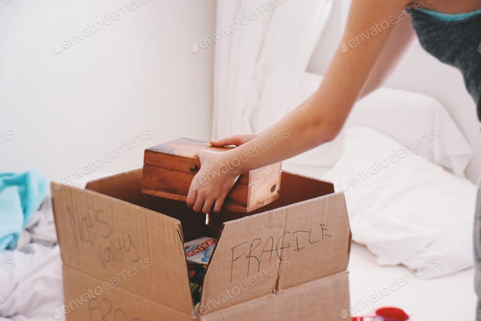 Mädchen packen eine Schachtel zum Bewegen  💲