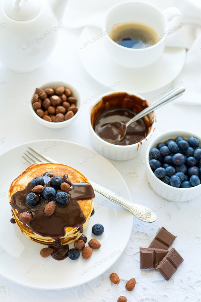Traditional breakfast concept. Stack of pancakes with chocolate sauce, blueberries and nuts on white