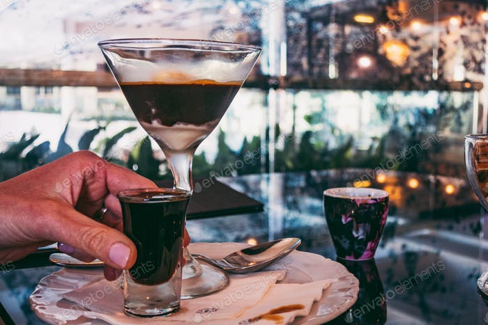 shot of liquor in hand, next to a glass of affogato, Italian coffee with ice cream
