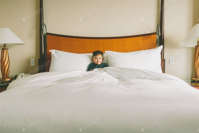 A boy relaxing in a  hotel bed.