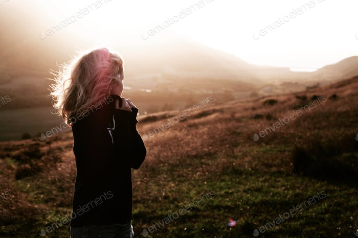 Girl looking out on golden sunset