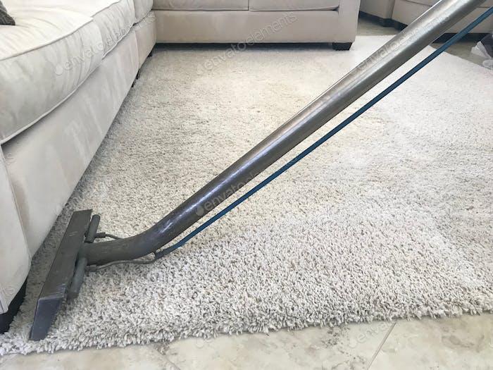 Ein Mann benutzt einen Shampooer, um einen weißen Teppich zu reinigen