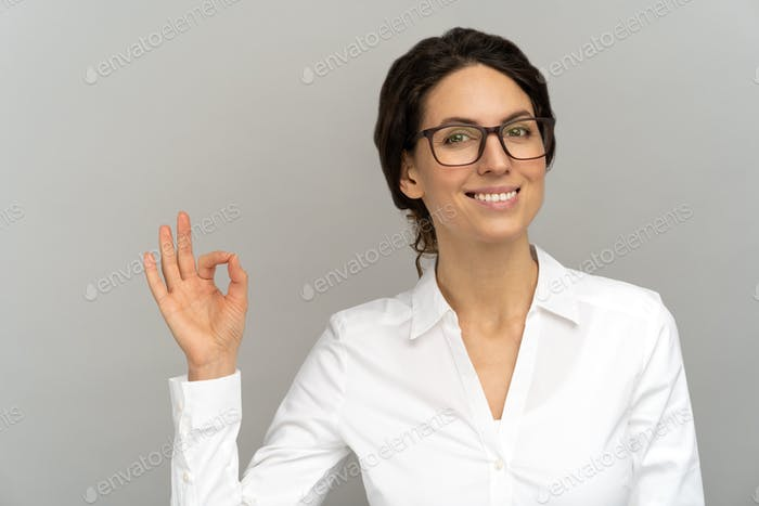 Cheerful business woman wear blouse in good mood smiling broadly, showing okay gesture in studio.