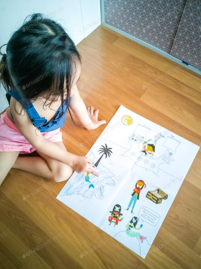 Cute little preschooler child drawing at home. Top view.