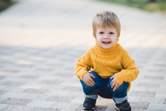 Funny baby girl 1-2 year old wearing knitted yellow sweater walking in autumn park outdoors close up