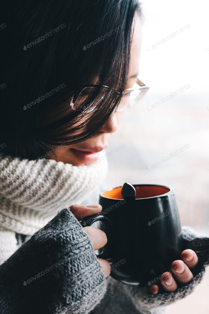 girl in sweater holding a hot cup of drink