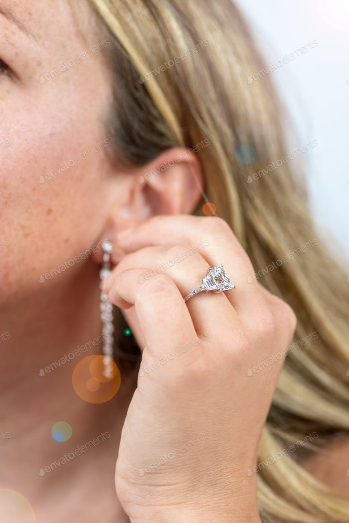 Woman getting ready and putting on diamond drop earrings for special romantic date night
