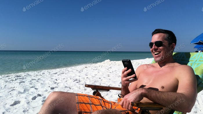 Millenial laughing at a text he received on beach from his dad...