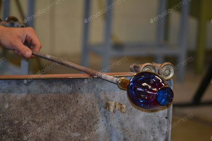 Man making a goblet by hand - blowing glass